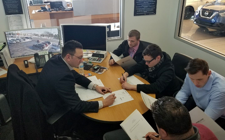 Phil Hellstrom (left), founder of Phelcan Group LLC and outreach specialist for Harper College's auto industry academic program, meets with sales consultants at M'Lady Nissan in Crystal Lake, Ill., for a weekly sales training session. 