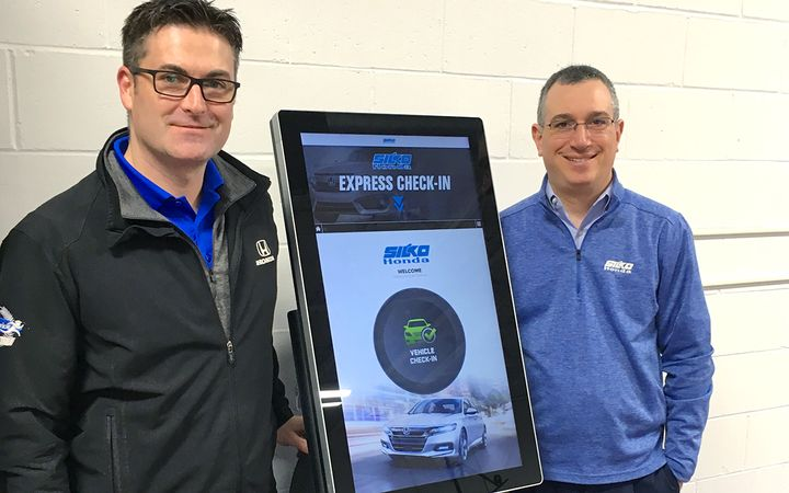 Director of Operations Geoff Ewell (left) and Vice President Adam Silverleib flank one of two GoMoto kiosks installed in the service drive at Silko Honda in Raynham, Mass. 