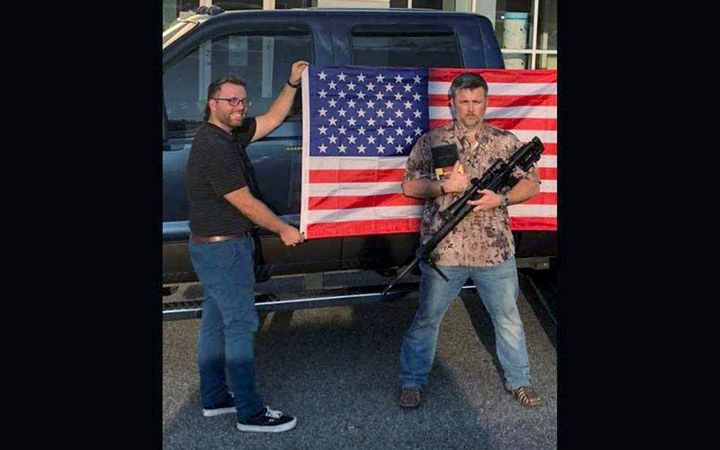 Christian Franks (left), a sales professional at Carolina Ford of Honea Path, S.C., poses with a customer. The dealership is offering a free American flag, Bible, and hunting rifle with the purchase of a new or used car. 