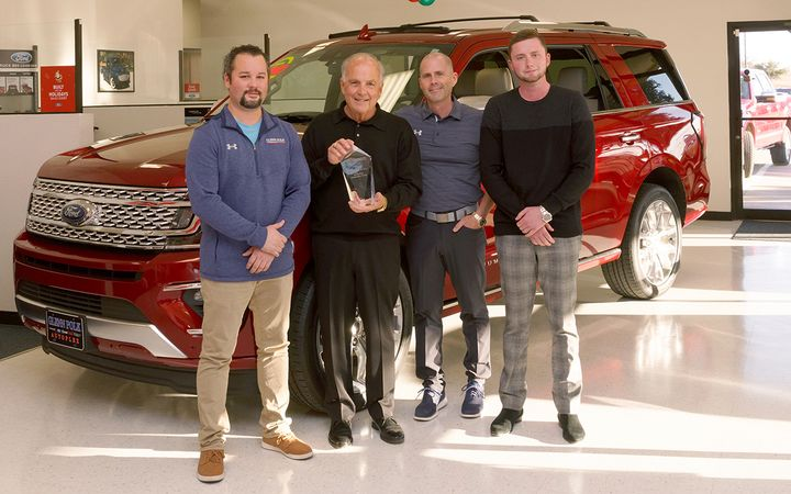 Glenn Polk Automotive's leadership team includes three generations of the Polk family. President and owner Glenn Ford (holding the 2019 F&I Dealer of the Year trophy) is flanked by sons Shawn and Trent Polk, both general managers and co-owners, and grandson Conner Polk, who serves as the group's pre-owned director.  - Photos by Gene's Photos (Gainesville, Texas)
