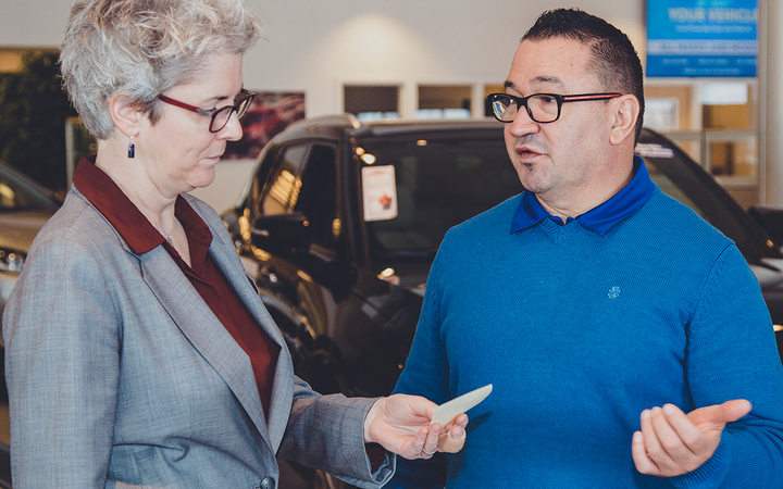 Church consults with Eric Williams, part of the four-person finance team at John Elway Chevrolet of Englewood, Colo. 