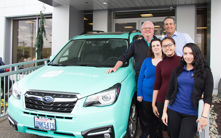 Brown stands beside Subaru of Puyallup's Joydrive-wrapped Outback with Joydrive Manager Rick Whyte and Equity Coordinating Specialists Kia Flint, Allyssa Riparip, and Nicki Moore. 