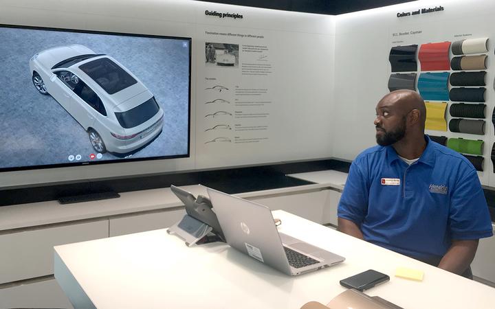 Sales Professional Herman McRae operates Hendrick Porsche's in-showroom custom vehicle configurator.   -