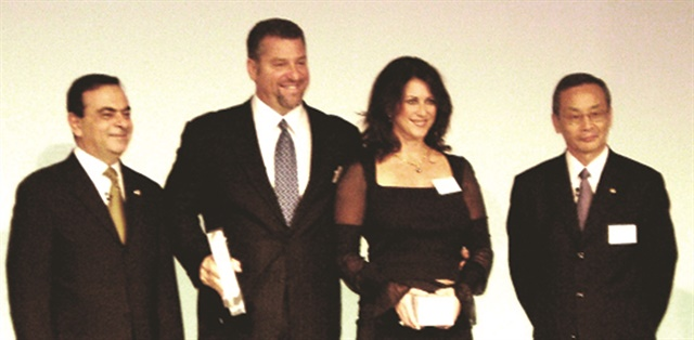 This 2003 photo shows Superior Automotive Group's Michael Kahn, standing with his wife, Tami Kahn, receiving the Nissan Global Achievement Award from Carlos Ghosn (left), chairman of Nissan Motor Co.'s board of directors, at the Palace Hotel in Tokyo. In May, an Orange County Superior County jury awarded Kahn $256.5 million in his eight-year contract dispute with floorplan lender Nissan Motor Acceptance Corp.