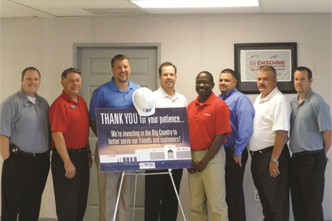 Star Dodge's sales management team poses with a sign about a dealership construction project.