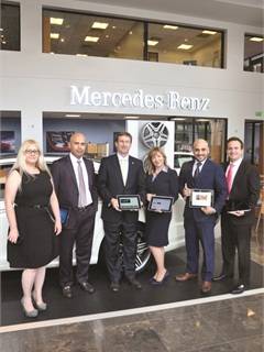 On the right, the dealership's F&I team members, including (from left ro right) Lourdes Guterriez, Mazher Majeed, Scott Cooper, Quintero, Guidi and Carlos Pedre, pose with the eMenu for iPad.
