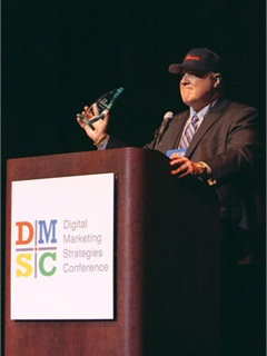 "Jim Ziegler accepts the ""Passion Award"" for lifetime achievement at the 2012 Digital Marketing Strategies Conference in Las Vegas. The award was presented by actor Adoni Maropis from TV drama ""24."""