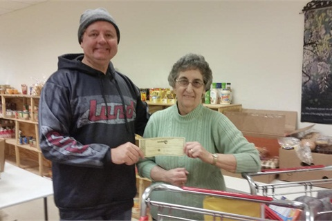 G.P. Anderson hands a check to Wadena Food Shelf Director Mary Ann Hagen.