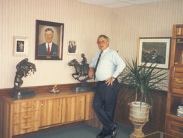 Ed in his office with a portrait of his father, Cyrill Bobit.